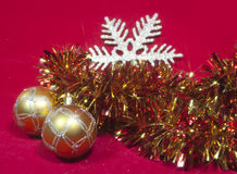 Two golden New Year's balls and ribbon on a red background Stock Photography
