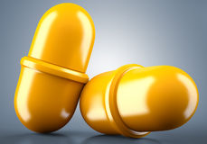 Two golden pills Stock Photography