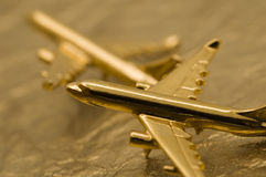 Two Golden Planes on Gold Foil. Macro of Two Golden Planes on Gold Foil Stock Image