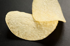 Two golden potato chips on the black, selective focus, close-up Stock Photography