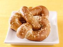 Two golden pretzels on a plate Stock Photography
