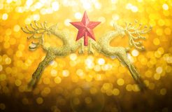 Two golden reindeer with red star on circular bokeh yellow gold background and copy space Royalty Free Stock Image