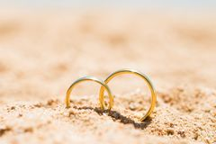Two Golden Rings In Sand. At Beach Royalty Free Stock Photo