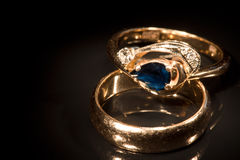 Two golden rings with sapphire and diamonds Royalty Free Stock Photography