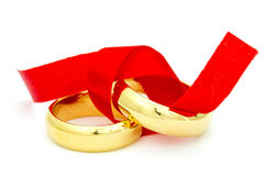 Two golden rings tied with red bow Stock Photo