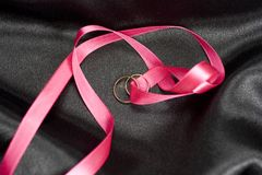 Two golden wedding rings. With pink ribbon Stock Photo