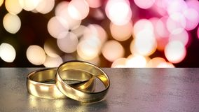 Two golden wedding rings on black table colored bokeh background Stock Image