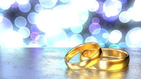 Two golden wedding rings on black table colored bokeh background Royalty Free Stock Images
