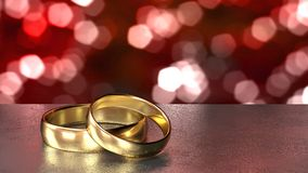 Two golden wedding rings on black table red bokeh background Stock Photography