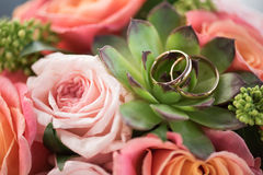 Two golden wedding rings on bouquet on roses and succulent. Wedding rings and flowers concept Royalty Free Stock Image