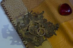 Two Golden wedding rings in a bowl of coconut peel. Two Golden wedding rings in a bowl of coconut rind, light falls on the side, painting a beautiful shadow stock image