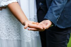 Two golden wedding rings on bride and groom`s palms. Wedding rings on the palm. Bride and groom hold wedding rings on their palms. During an engagement ceremony Stock Photo