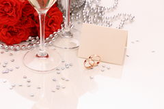 Two golden wedding rings with card, champagne glasses Royalty Free Stock Image