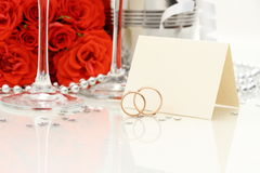 Two golden wedding rings with card, champagne glasses Stock Photo