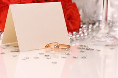 Two golden wedding rings with card, red roses. Two golden wedding rings with card, champagne glasses, red roses Royalty Free Stock Photo