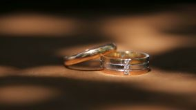 Two Golden wedding rings close-up. Two Golden wedding rings close-up on a wooden surface with a sun glare stock footage
