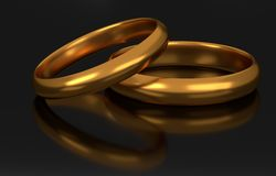 Two golden wedding rings on dark background. Two golden wedding rings on dark reflective surface Stock Photography