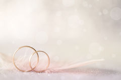 Two Golden Wedding Rings and Feather - light soft background Stock Images