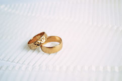 Two golden wedding rings on light ribbon background Royalty Free Stock Photography