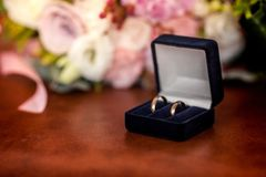 Two golden wedding rings in a orange box. Accessory stock photo