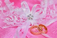 Weeding rings. Two golden wedding rings on the pink background Royalty Free Stock Image