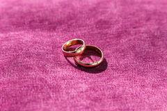 Two golden wedding rings on purple brocade Royalty Free Stock Images