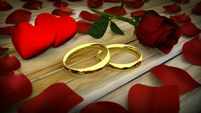 Two golden wedding rings and red rose with petals. On wooden table stock footage