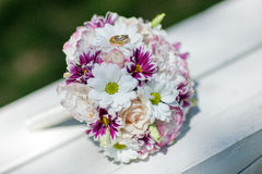 Two golden wedding rings on the spring flowers bouquet. Royalty Free Stock Photo