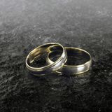 Two golden wedding rings on stone surface Royalty Free Stock Image