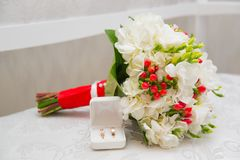 Two Golden wedding rings in white box and bouquet with white flowers and red berries. Two Golden wedding rings in white box and bouquet with white flowers and stock images