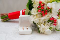 Two Golden wedding rings in white box and bouquet with white flowers and red berries. Two Golden wedding rings in white box and bouquet with white flowers and royalty free stock images