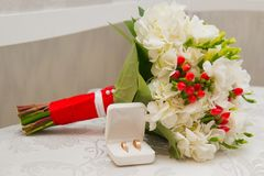 Two Golden wedding rings in white box and bouquet with white flowers and red berries. Two Golden wedding rings in white box and bouquet with white flowers and stock photos