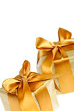 Two golden wrapped gift boxes. Two gift boxes in gold wrapping paper with ribbons and bows Royalty Free Stock Images