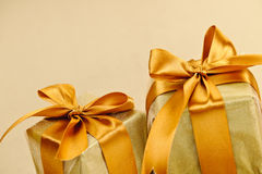 Two golden wrapped gift boxes. Two gift boxes wrapped in gold ribbons with copy space Royalty Free Stock Photos