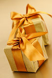 Two golden wrapped gift boxes. Two gift boxes in gold wrapping paper with ribbon and bow Stock Photography