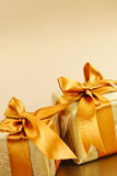 Two golden wrapped gift boxes. Two gift boxes wrapped in gold ribbons with copy space Stock Photo