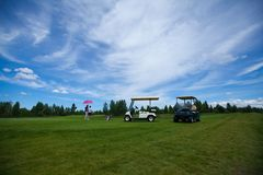 Two golf carts on the golfe course in summer. With couple royalty free stock photo