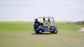 Two golf carts loaded with bags and equipment. Parked on a fairway on a golf course with a player visible in the distance stock video