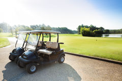 Two golf-carts standing at parking of golf club. Two electric golf-carts standing at the parking lot of golf club at sunny day Stock Photos
