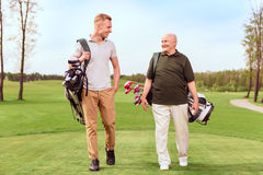 Two golf players walking through course Stock Photo