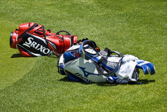 Two Golfers Club Bags. Two Golf Club Bags, lying on their sides, just off the edge of the green Royalty Free Stock Photo