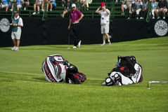 Two Golfers Club Bags. Two Golf Club Bags, lying on there sides, just off the edge of the green Stock Images