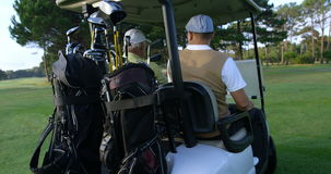 Two golfers driving in their golf buggy stock video