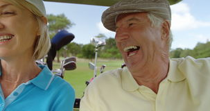 Two golfers driving in their golf buggy stock video footage