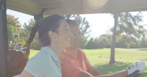 Two golfers driving in their golf buggy stock footage