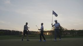 Two golfers with junior golfers walking on perfect golf course at sunset day stock footage