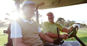 Two golfers laughing together in their golf buggy stock footage
