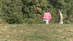 Two golfers practicing swing in the rough. A view or scene of Golf stock video footage