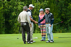 Two golfers shake hands on golf feeld Royalty Free Stock Photography