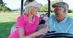 Two golfers taking a selfie in golf buggy. At golf course stock video